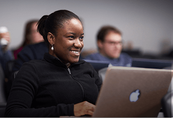 Smiling Student in class with an Apple laptop